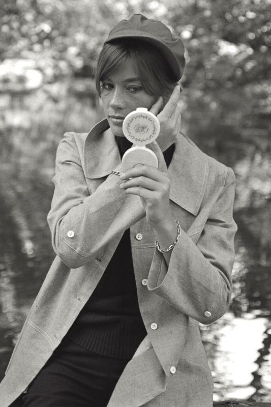 The French singer Françoise Hardy arranging her hair with the help of a handmirror, leaning against a wooden fence on the banks of a small lake in the gardens of Milan; the singer is in Italy for the resumption of the filming of 'Grand Prix' by John Frankenheimer, her third acting experience. Milan, summer 1966. (Photo by Mario De Biasi/Mondadori Portfolio via Getty Images)
