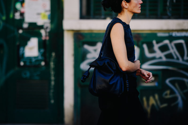 Woman wearing dark outfit with black bag