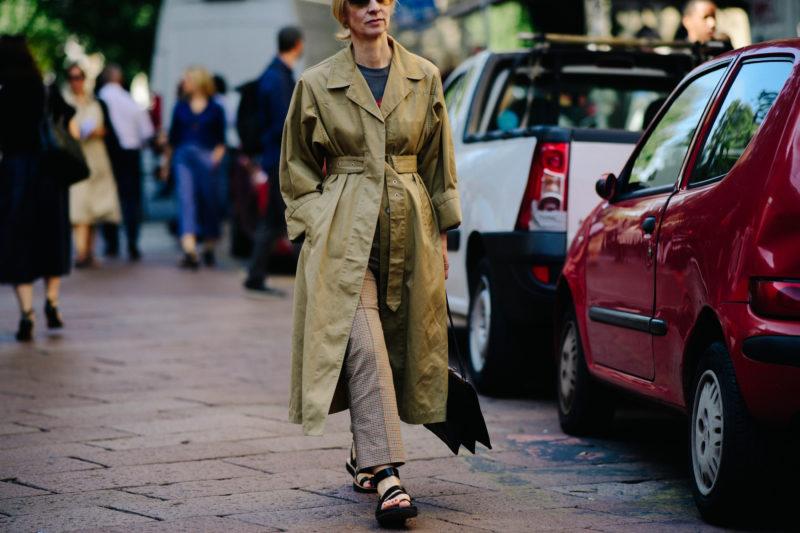 Woman walking in tan trench coat