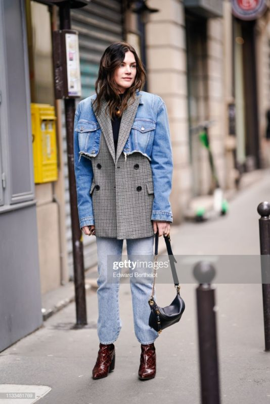 PARIS, FRANCE - MARCH 03: Madelynn Furlong wears a blue denim ripped jacket ver a checked blazer jacket, blue jeans, a black leather fanny pack bag, burgundy shoes, outside Thom Browne, during Paris Fashion Week Womenswear Fall/Winter 2019/2020, on March 03, 2019 in Paris, France. (Photo by Edward Berthelot/Getty Images)